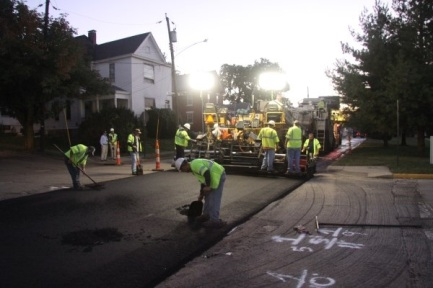 Workers smoothing rubber modified asphalt around manholes. Photo by Mark Belshe, RPA.