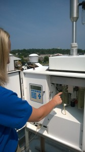 DAQ environmental inspector Jennifer Brown points to a cylindrical magazine that holds sample filters inside a PM2.5 monitor in Somerset, KY.