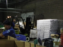 Employees at the state's recycling center prepare to load bales of white paper for delivery.